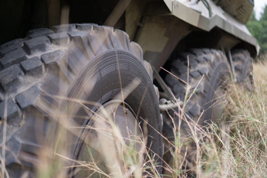 Wheels of armored personnel carrier in the grass field